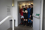 The players and match officials pictured outside the dressing rooms before Gala Fairydean Rovers (in red) host Gretna 2008 in a Scottish Lowland League match at Netherdale, Galashiels. The home club were established in 2013 through a merger of Gala Fairydean, one of Scotland's most successful non-League clubs, and local amateur club Gala Rovers. The visitors were a 'phoenix' club set up in the wake of the collapse of the original club, which had competed for a short time in the 2000s before going bankrupt. The home aside won this encounter 4-1 watched by a crowd of 120 at a stadium which features one of the country's most notable stands, a listed building constructed in 1964 but at the time of this fixture closed to spectators on safety grounds.