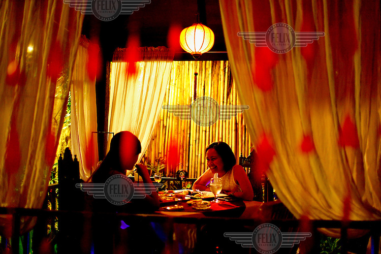 Two women eat a meal in a restaurant.