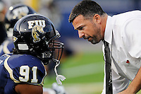 11 October 2008:  FIU Head Football Coach Mario Cristobal speaks with linebacker Armond Willis (91) during warm-ups prior to the FIU 31-21 victory over Middle Tennessee at FIU Stadium in Miami, Florida.