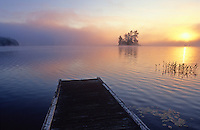 Canada, Ontario, Lake MacKay, sunrise over lake with island in distance and pier in foreground