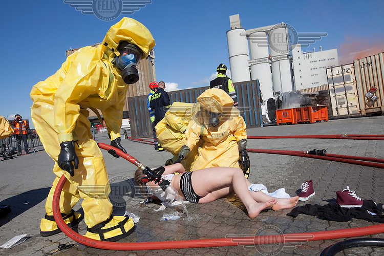 Paramedics in HAZMAT (hazardous material) suits hose down a &quot;victim&quot; supposedly exposed to chemicals. HarbourEx15, a field training exercise with scenarios connected to operations in the harbor April 27th &ndash; 29th 2015.<br />