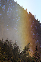 A rainbow glows when morning sunlight filters through blowing ice crystals.