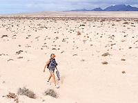 Spain, ESP, Canary Islands, Fuerteventura, Istmo de La Pared, 2012Oct13: A female tourist hikes in the desert of the Istmo de La Pared.