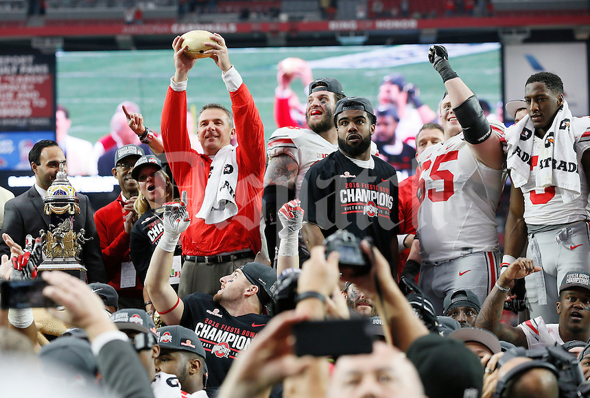 Ohio State Buckeyes head coach Urban Meyer hoists the trophy following Ohio State's 44-28 win over the Notre Dame Fighting Irish in the Battlefrog Fiesta Bowl at University of Phoenix Stadium in Glendale, Arizona on Jan. 1, 2016. (Adam Cairns / The Columbus Dispatch)