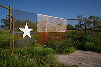 Rural country landscape with Texas Lone Star Flag Design on metal fence gate