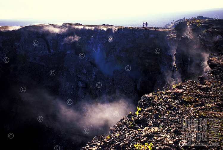 Two people hiking on lava rock with steam from lava vents near Kilauea volcano at Hawaii volcanoes national park
