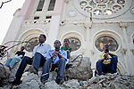 People sit on top of the rubble of the destroyed national cathedral for a church service on July 11, 2010 in Port-au-Prince, Haiti.