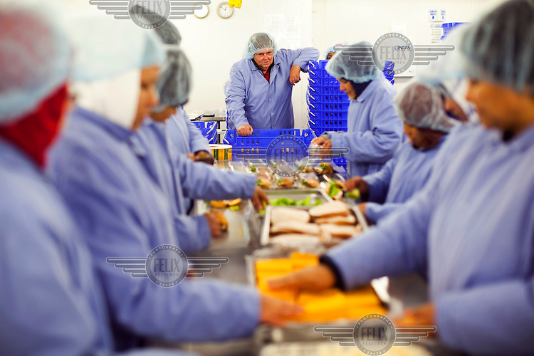 Workers, dressed in food hygiene workwear, at Greencore's Cincinnati facility make sandwiches. Greencore Group is an Irish-based company that produces convenience foods and sandwiches throughout Britain and Europe. In 2008 Greencore acquired Home Made Brand Foods in Newburyport, Massachusetts to establish Greencore North America.
