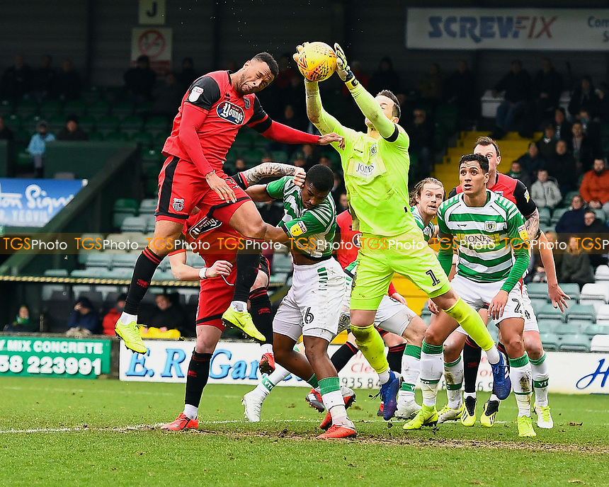 Yeovil Town keeper Stuart Nelson takes the ball off the head of Wes Thomas of Grimsby Town during Yeovil Town vs Grimsby Town, Sky Bet EFL League 2 Football at Huish Park on 9th February 2019