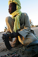 an SLA ( sudan liberation army) child soldier practices regulare maintenence to his weapon in a forwading base near the cahdian borader in north darfur on Nov 2004.