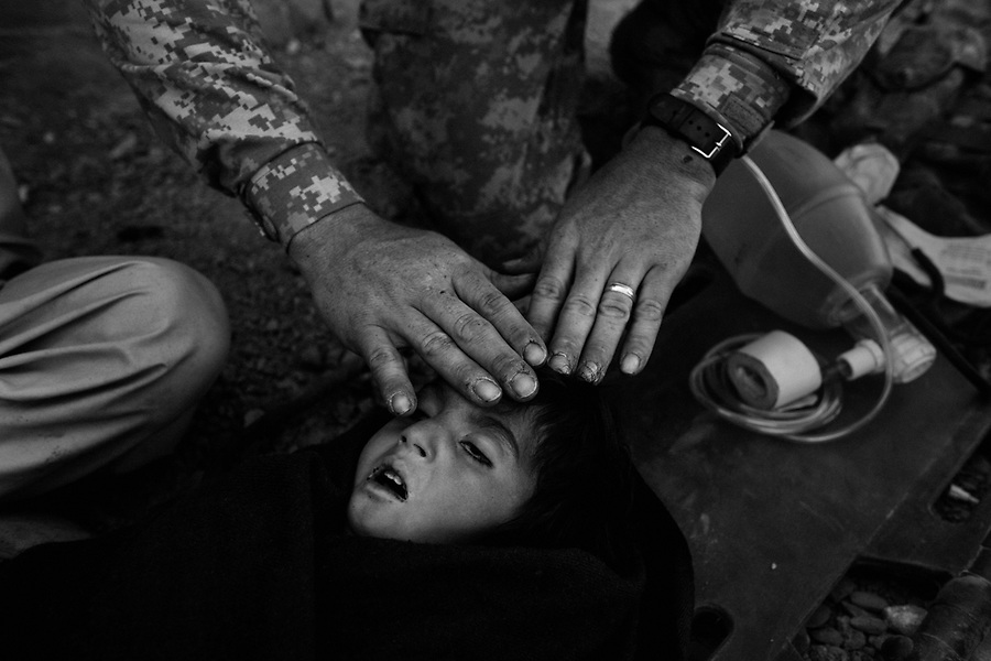 A medic with the 101st Airborne Division places his hand on the forehead of an Afghan child who has died from an unknown respiratory ailment despite his attempts at CPR after the child's father brought the boy to the Spera District Center (DC) in the hopes that US and Afghan forces would be able to treat the child on Monday October 27, 2008. The Spera DC is less than a dozen miles from the Afghan-Pak border.