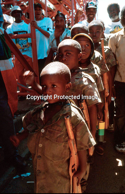 dippchi00125 Children.  A youth group from Alexandra, a poor township in Johannesburg, are  marching to honor ANC freedom fighters during the struggle at a rally in Soweto, South Africa. South African's voted on June second 1999. Toy guns held by children.©Per-Anders Pettersson/iAfrika Photos