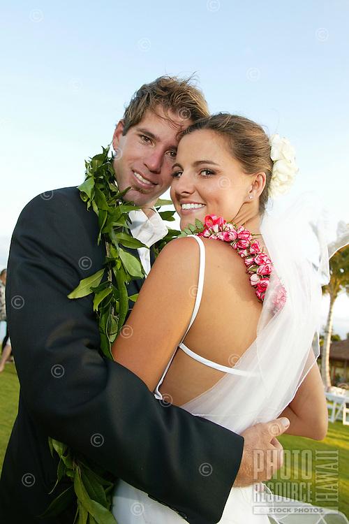 Bridal couple hugging, smiling looking back at the camera