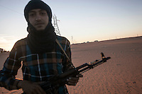 November 23, 2014 - Ubari region, Libya: A Tuareg tribal fighter from Mali stands guard at one of the check points of Al-Sharara oilfield installations powered off weeks ago in the Southwest of Libya. Fighting around Southwest Ubari region ignited after Tuareg militias from Mali and Libya sized control over the vast oilfield installations aligned with the Third Force of Misrata armed forces. Since then raged battles have taken place between two factions: one faction of Tuareg fighters lead by Third Force from Misrata pushing to clean the region from the other faction of Tebu tribal fighters defending their controlled territory. (Photo/Narciso Contreras)