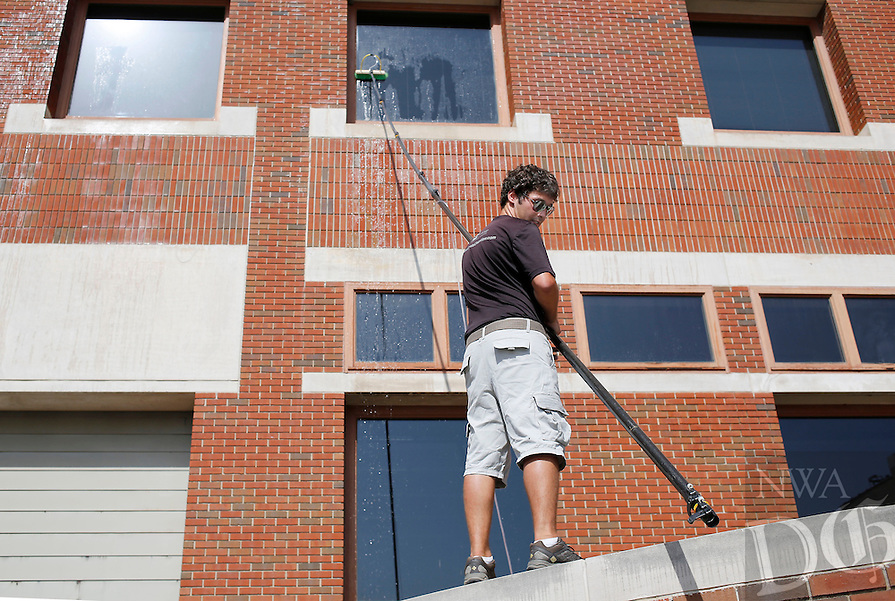 NWA Media/DAVID GOTTSCHALK - 8/20/14 - Jordan Bannantine, a crew worker with Crystal Clean of Ames, IA., contracted by Squeegee Squad, moves along an edge as he uses a water fed pole to clean the top windows on the east side of the East Square Plaza Building in Fayetteville Wednesday August 20, 2014. Bannantine was working with Shane Henderson, crew chief with Crystal Clean, on the job.