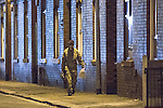 © Joel Goodman - 07973 332324 . No syndication permitted . 28/11/2013 . Manchester , UK . A man in army fatigues walks towards the house with bags and a torch . Scene at 17 Mellor Street in Eccles , Greater Manchester this evening (Thursday 28th November 2013) where police have cordoned off adjoining streets and evacuated houses following the discovery of a suspicious device .  Photo credit : Joel Goodman