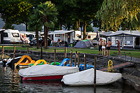 Switzerland. Canton Ticino. Tenero. Camping Campofelice. Motorhomes, caravans and private boats in harbor. A family seats in front of caravan while other campers enjoy a walk near the water. A campervan (or camper van), sometimes referred to as a camper, or a caravanette, is a self-propelled vehicle that provides both transport and sleeping accommodation. A motorhome (or motor coach is a type of self-propelled recreational vehicle (RV) which offers living accommodation combined with a vehicle engine. Motorhomes are part of the much larger associated group of mobile homes which includes caravans, also known as tourers, and static caravans. A caravan, travel trailer, camper or camper trailer is towed behind a road vehicle to provide a place to sleep which is more comfortable and protected than a tent. It provides the means for people to have their own home on a journey or a vacation. Campers are restricted to designated sites for which fees are payable. 19.07.2018 © 2018 Didier Ruef