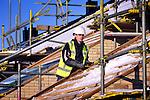 Doorwerken tijdens een koude vorstperiode op een bouwplaats in de winter betekent warm gekleed zijn met capuchon onder de bouwhelm, sjaal om en handschoenen aan. COPYRIGHT TON BORSBOOM