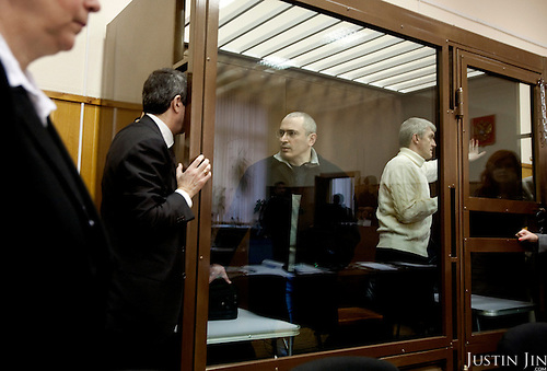 Former Yukos oil giant CEO Mikhail Khodorkovsky talks to his lawyer at a court room in Moscow, Russia, Tuesday, March 31, 2009. The trial begins Tuesday for former oil tycoon Mikhail Khodorkovsky and business partner Platon Lebedev..Khodorkovsky's supporters claim this trial is just a new phase of a reprisal campaign driven by political calculations, commercial interests and personal motives. A new conviction and sentence would send a signal that nothing has changed despite President Medvedev's words, they say, while an acquittal would mark a break with the Putin era.