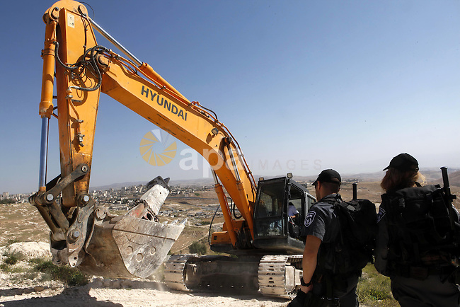 Israeli security forces stand guard as Jerusalem municipality workers use bulldozers to demolish a Palestinian home owned by Ghaith family in the mostly Arab east Jerusalem neighbourhood of al-Tur on April 29, 2013. Palestinian homes built without an Israeli construction permit are often demolished by order of the Jerusalem municipality. Photo by Sliman Khader