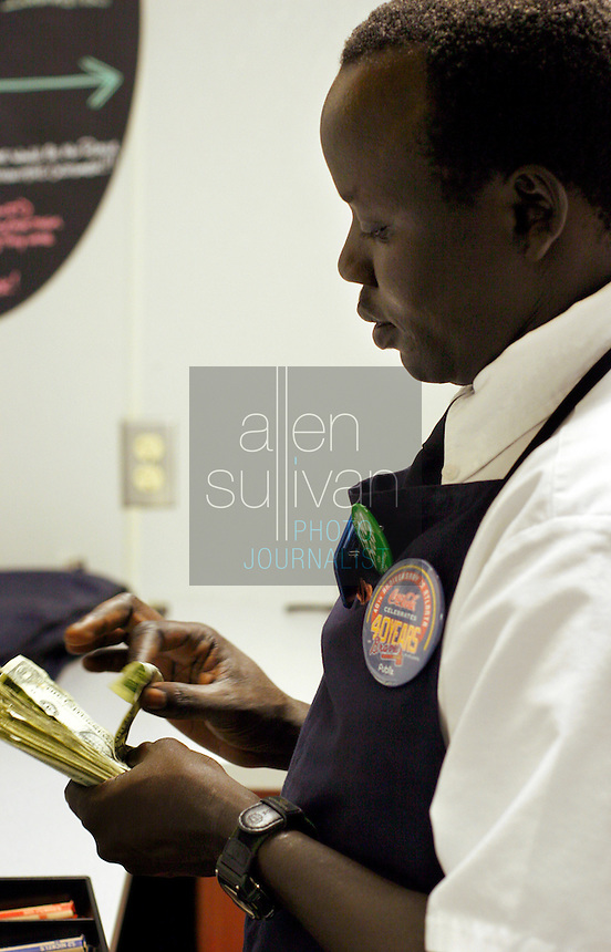 """John Madut (cq) counts a cash drawer at the start of his shift at the Toco Hills Publix on Friday, Sept. 1, 2006. One of the """"Lost Boys of Sudan,"""" Madut has worked at the grocery store since 2003. This year he returned to Sudan for the first time since leaving and saw that his home town is in desperate need of clean drinking water. He's trying to help by raising funds for a new well, but has found the effort to be a financially monumental task."""