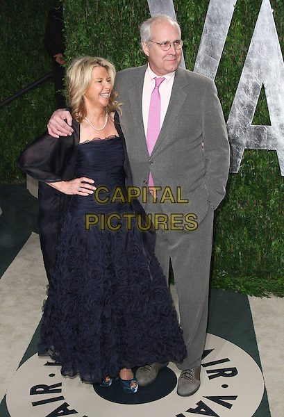 Jayni Chase & Chevy Chase.2012 Vanity Fair Oscar Party held at the Sunset Tower West Hollywood, California, USA..26 February 2012.oscars full length dress blue ruffle frills grey gray suit married husband wife .CAP/ADM/FS.©Faye Sadou/AdMedia/Capital Pictures.