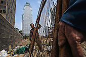 Former farmers build a new high-rise -- on a plot that was farmland just a few years ago -- in Linyi city in the northeastern China. <br /> <br /> The local government is razing down this village on the outskirts of the city and turning farmland into an urban development zone. <br /> <br /> China is pushing ahead with a dramatic, history-making plan to move 100 million rural residents into towns and cities between 2014 and 2020 &mdash; but without a clear idea of how to pay for the gargantuan undertaking or whether the farmers involved want to move.<br /> <br /> Moving farmers to urban areas is touted as a way of changing China&rsquo;s economic structure, with growth based on domestic demand for products instead of exporting them. In theory, new urbanites mean vast new opportunities for construction firms, public transportation, utilities and appliance makers, and a break from the cycle of farmers consuming only what they produce.<br /> <br /> Urbanization has already proven to be one of the most wrenching changes in China&rsquo;s 35 years of economic reforms. Land disputes rising from urbanization account for tens of thousands of protests each year.