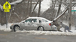 Michael Fuehne (left) and David Fellner Jr., both of Belleville, strain as they push the car of Billy Brownlee out of a pile of snow after Brownlee got sideways turning from Robin Hill Lane onto McClintock Avenue in Belleville on Saturday morning January 12, 2019. People were busy digging out -- and some were having fun -- after a major snowstorm hit the St. Louis metropolitan region. <br /> Photo by Tim Vizer