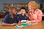 Caucasian female teacher with red hair shows excitement about learning impaired black male student's progress with reading while Vietnamese 7+ boy looks on