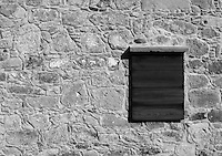 Wooden window on a stone-wall stock image in black and white.<br />