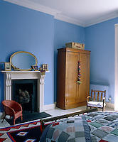 A patchwork quilt on the bed and walls painted a cornflower blue give this bedroom a tranquil country feel