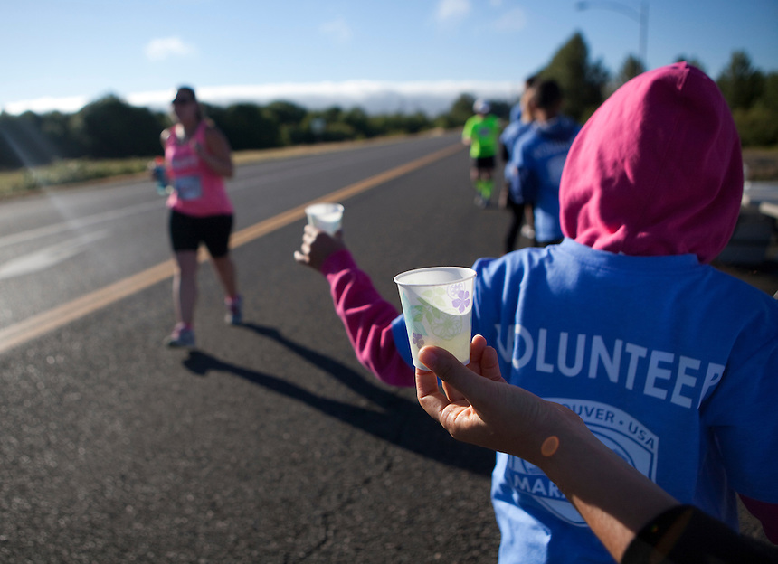 Volunteers offer water to runners taking part in the Vancouver Marathon, near Vancouver Lake Sunday June 19 2016. (Photo by Natalie Behring for the Columbian)