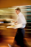 CANADA, Vancouver, British Columbia, a waiter delivers food at the Four Seasons restaurant Yew
