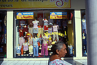 A Yucateca womanwalks by a colorful window display of a clothing store in Merida, Yucatan, Mexico