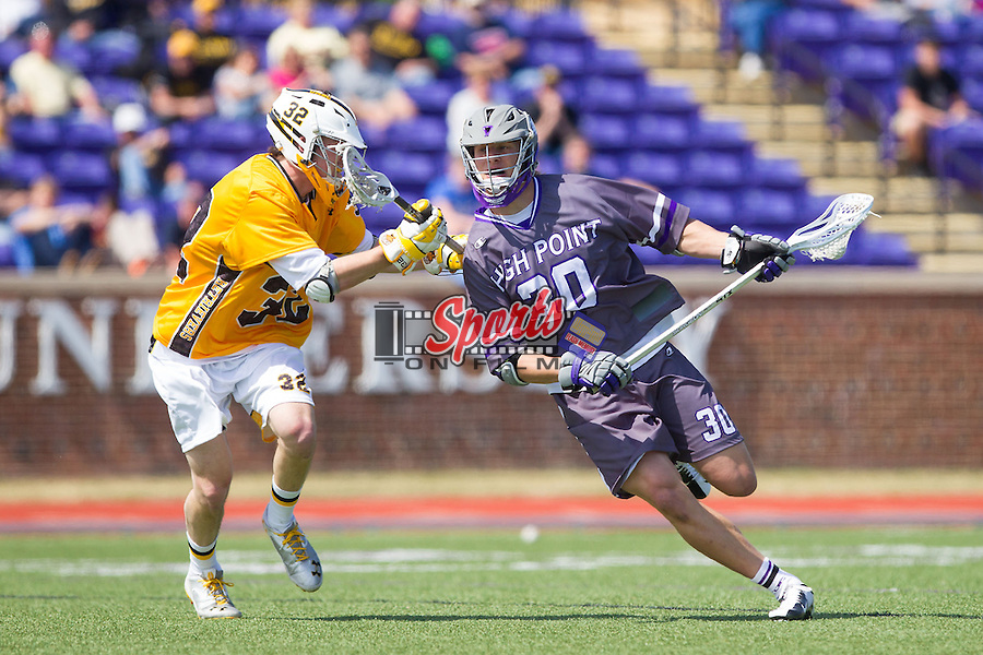 Tyler Cook (30) of the High Point Panthers is checked by Steve Winsor (32) of the UMBC Retrievers at Vert Track, Soccer & Lacrosse Stadium on March 15, 2014 in High Point, North Carolina.  The Panthers defeated the Retrievers 17-15.   (Brian Westerholt/Sports On Film)