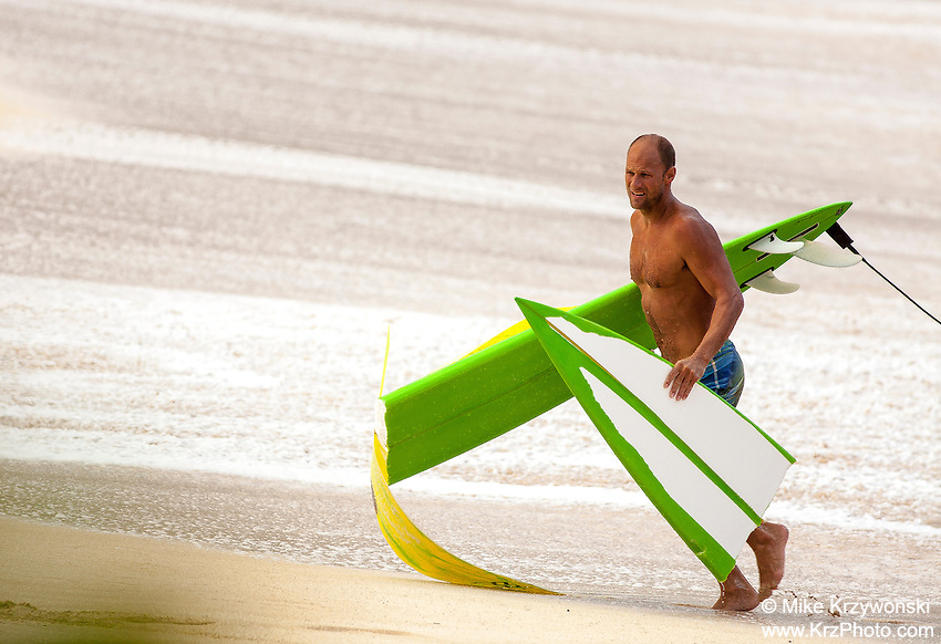 A Caucasian surfer walking on the beach with a broken surfboard after surfing big waves at Waimea Bay on the North Shore, O'ahu