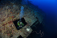 Diver coming out of hatch on ship wreck Mairi Bahn, aka Windjammer, Bonaire, Netherlands Antilles, Caribbean, Atlantic, model release