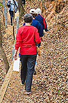 Senior women in casual clothing walk in single line hiking on pathway of fallen leaves in William Faulkner 's Rowan Oak Woods in Oxford, Mississippi