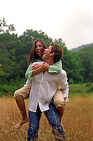 Young man giving a woman a piggy back ride