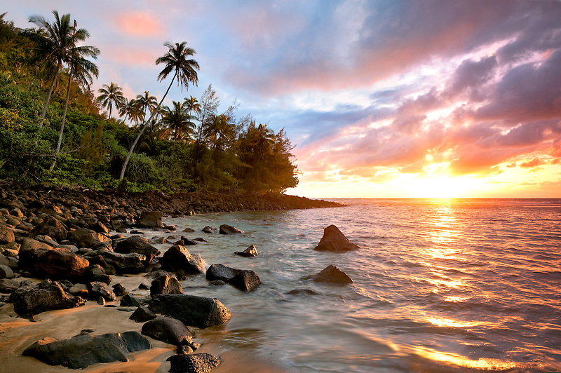 Sunset at Kee Beach with palm trees. Kauai, Hawaii.