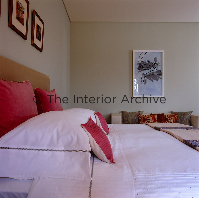 Pale grey walls in the bedroom are punctuated with touches of red and yellow ochre in the soft furnishings