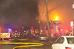 March 1, 2014 - Huntington, New York, U.S. - Fire rages in the heart of Huntington village, on New York Avenue. Firefighters came from many surrounding towns of Suffolk County, Long Island, and huge clouds of smoke lit up the night sky for blocks.