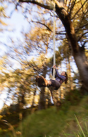 Motion shot of woman with eyes closed swinging on rope swing, Olympic National Park, Coastal Strip, Olympic National Park, WA.