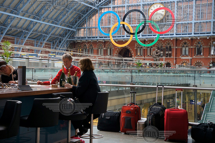 The Olympic rings at London St Pancras International Station with passengers drinking at the Champagne Bar.