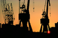 © David Paterson.Silhouette of dockside cranes against an evening sky, port of Cadiz, southern Spain...