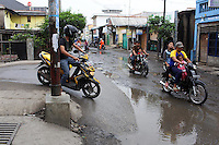 Indonesians riding small motorbikes in Jakarta.<br />