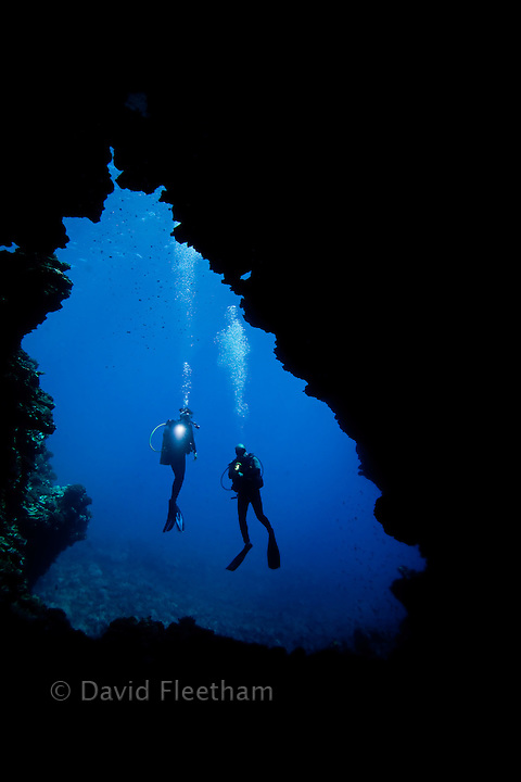 Divers (MR) pictured at one of the openings to First Cathedral off the Island of Lanai, Hawaii.