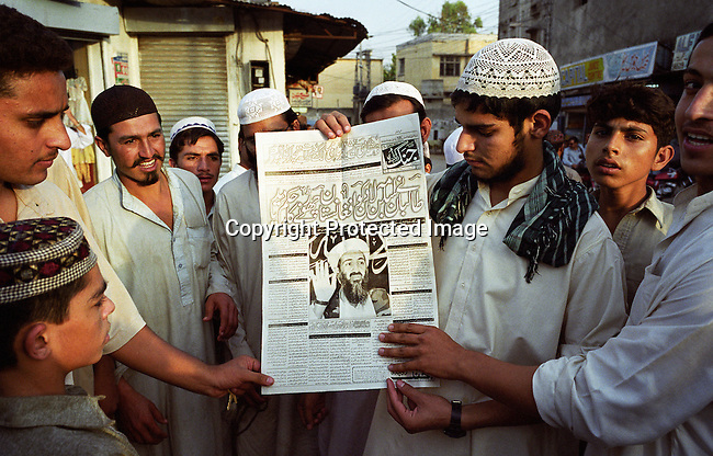 Youths supporters of Taliban looks at a newspaper cover with Osama Bin Laden photo on September 20, 2001 outside Jamia Islamia mosque in central Rawalpindi, about 15 kilometers outside Islamabad, Pakistan. Most of the youths attend Sipah-e Sahaba a religious school in the area, known for educating future Taliban members. (Photo by: Per-Anders Pettersson)