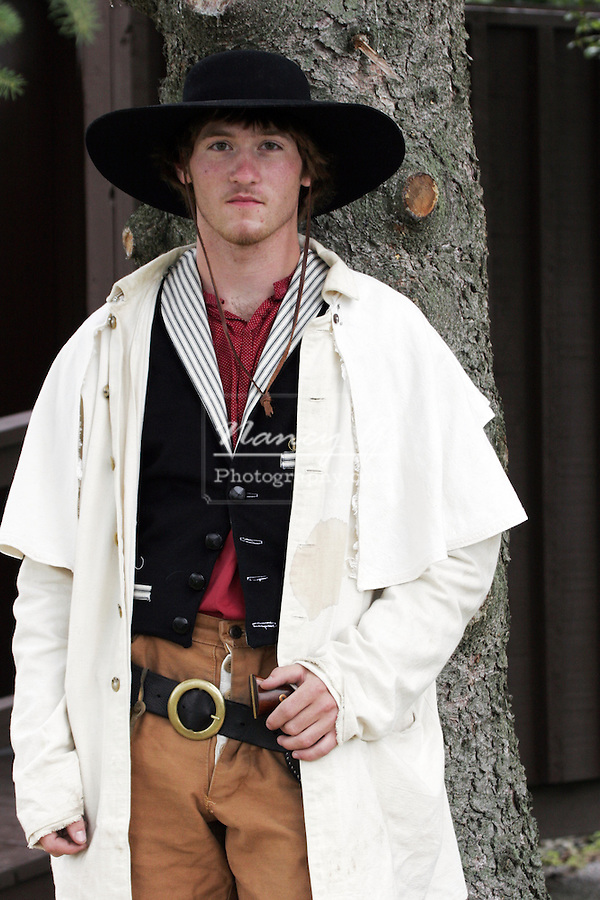 A young cowboy holding his gun in the holster at a 1800s western reenactment