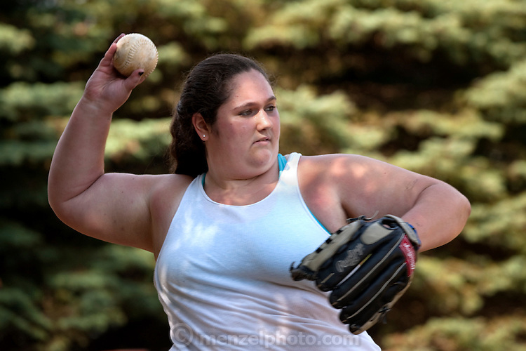 Mackenzie Wolfson, a natural athlete and accomplished tennis player and a member of her school's varsity softball team, plays softball at Camp Shane, Catskill Mountains, New York. (From the book What I Eat: Around the World in 80 Diets.) The caloric value of her typical day's worth of food in July was 1,700 kcals. She is 15; 5 feet nine inches tall,  and 299 pounds.  MODEL RELEASED.